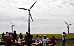 Landschaft mit Windkraftanlagen. Vorn rastet Bike for Peace and New Energies an gedeckten Tischen.